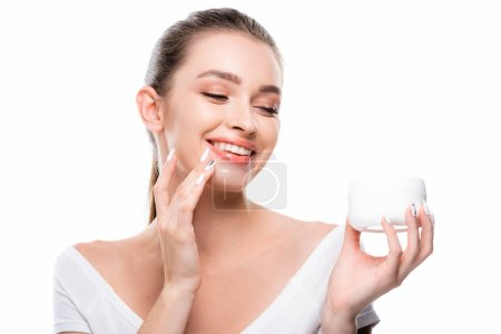 Photo pour Beautiful, smiling girl applying cosmetic cream on face isolated on white - image libre de droit