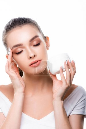 Photo pour Beautiful girl applying face cream with closed eyes isolated on white - image libre de droit