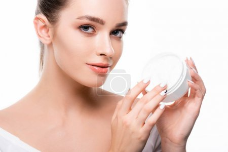 Photo pour Attractive girl looking at camera while touching face cream in container isolated on white - image libre de droit