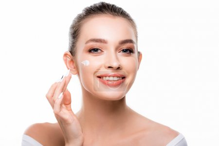 Photo pour Attractive, smiling woman applying cosmetic cream on face and looking at camera isolated on white - image libre de droit