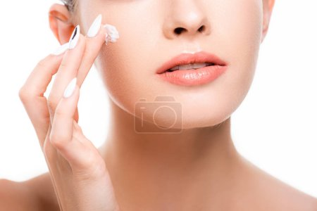 Photo pour Cropped view of young womam applying cosmetic cream on face isolated on white - image libre de droit
