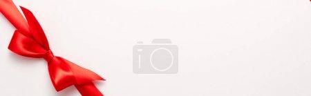 Photo pour Plan panoramique de ruban de satin rouge avec noeud sur blanc - image libre de droit