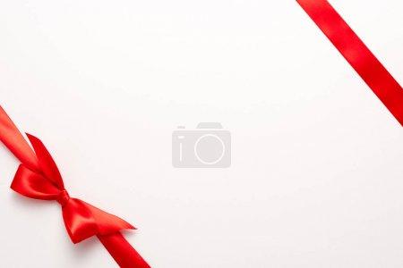 Photo pour Vue du dessus du ruban de satin rouge avec noeud sur blanc - image libre de droit