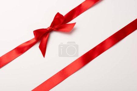 Photo pour Vue du dessus du ruban rouge avec noeud en satin sur blanc - image libre de droit