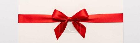 Photo pour Prise de vue panoramique de noeud en satin rouge sur enveloppe isolée sur blanc - image libre de droit
