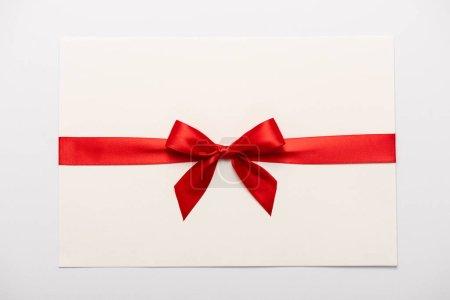 Photo pour Vue de dessus de l'arc en satin rouge sur enveloppe isolée sur blanc - image libre de droit