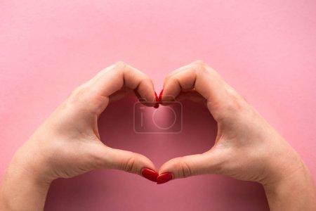 cropped view of woman showing heart-shaped sign with hands on pink