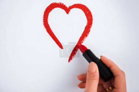 Photo for Cropped view of woman drawing heart while holding red lipstick isolated on white - Royalty Free Image