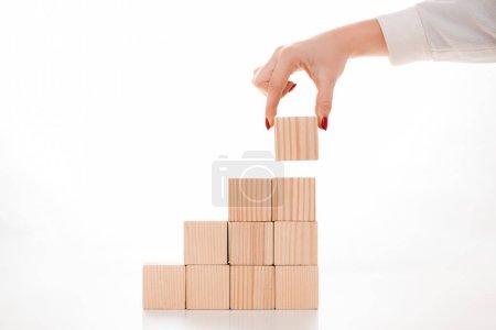 Photo pour Cropped view of businesswoman holding wooden cube on white - image libre de droit