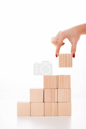 Photo for Cropped view of woman putting wooden cube on white - Royalty Free Image