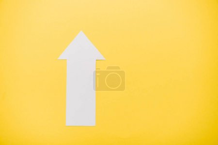 Photo pour Top view of white arrow isolated on yellow with copy space - image libre de droit