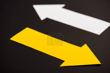 Photo for Selective focus of yellow directional arrow isolated on black - Royalty Free Image