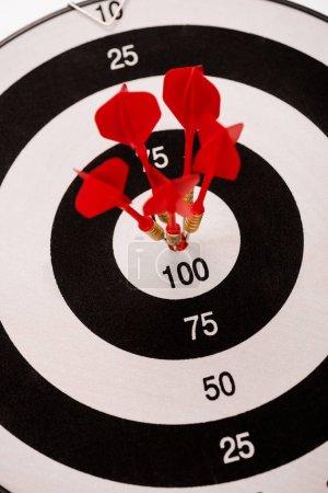 Photo pour Selective focus of black and white dartboard with red arrows - image libre de droit