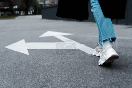 Photo for Cropped view of woman in jeans walking near directional arrows on asphalt - Royalty Free Image