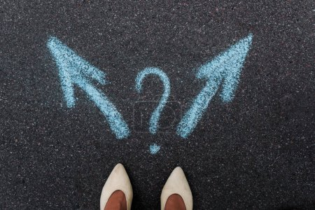 Photo pour Top view of woman standing near blue directional arrows and question point on asphalt - image libre de droit