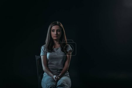 Photo for Despaired woman looking away while sitting on chair in darkness isolated on black - Royalty Free Image
