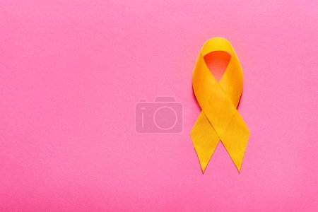 Photo pour Top view of yellow awareness ribbon on pink background, suicide prevention concept - image libre de droit