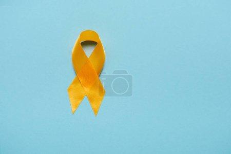 Photo pour Vue du haut du ruban de sensibilisation jaune sur fond bleu, concept de prévention du suicide - image libre de droit