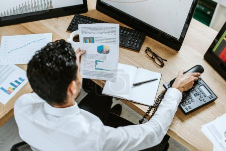 Photo for Overhead view of bi-racial trader looking at paper and holding handset - Royalty Free Image