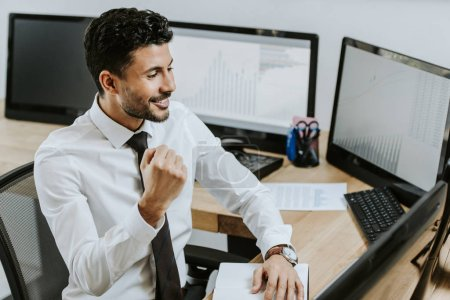 Photo for High angle view of bi-racial trader showing yes gesture and looking at computer - Royalty Free Image