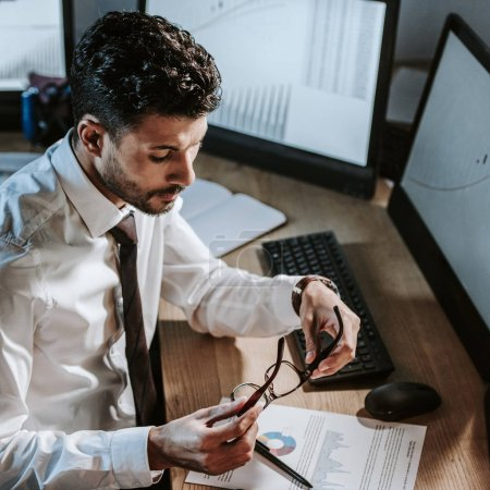 Photo for High angle view of bi-racial trader looking at paper and sitting near computers with graphs - Royalty Free Image