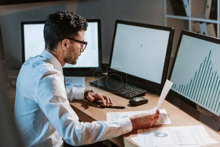 Photo for Bi-racial trader looking at computer with graphs and holding paper - Royalty Free Image