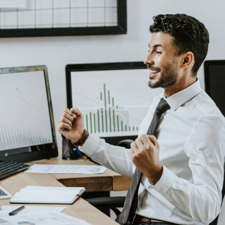 Photo for Side view of smiling bi-racial trader showing yes gesture and sitting near computers - Royalty Free Image