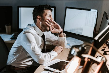 Photo for Bi-racial trader yawning and sitting near computer with graphs - Royalty Free Image
