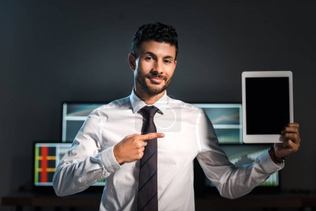 Lächelnder Händler zeigt mit Finger auf digitales Tablet