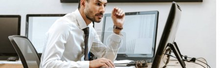 Photo for Panoramic shot of bi-racial trader looking at computer and sitting near computer with graphs - Royalty Free Image