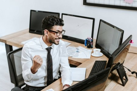 Photo for High angle view of smiling bi-racial trader showing yes gesture and looking at computer - Royalty Free Image