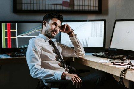 Photo pour Souriant bi-racial commerçant assis près des ordinateurs avec des graphiques dans le bureau - image libre de droit