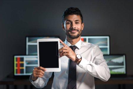 Photo pour Souriant bi-racial commerçant tenant tablette numérique et les ordinateurs avec des graphiques sur fond - image libre de droit