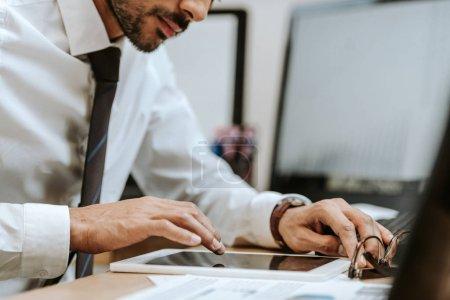 Photo pour Crochet vu d'un commerçant biracial assis à une table et utilisant une tablette numérique - image libre de droit