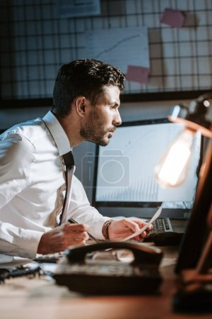 Photo for Side view of handsome bi-racial trader using computer and sitting at table - Royalty Free Image