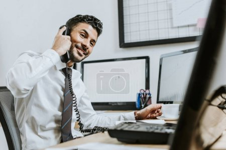 Photo for Smiling bi-racial trader talking on telephone and sitting at table - Royalty Free Image