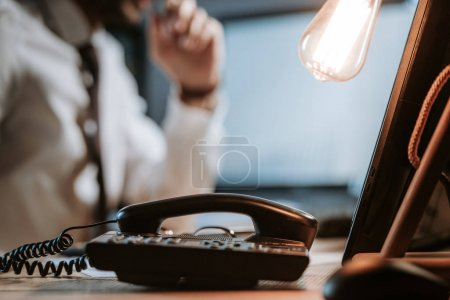Photo for Selective focus of lamp and telephone on wooden table - Royalty Free Image