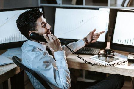 Photo pour Un commerçant bi-racial souriant parlant au téléphone et assis à table - image libre de droit