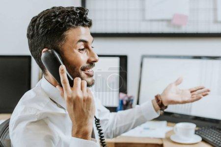 Photo pour Vue latérale d'un commerçant bi-racial souriant parlant au téléphone - image libre de droit