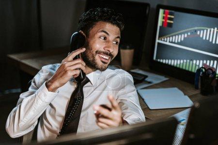 Photo pour Un commerçant bi-racial souriant parlant au téléphone et détournant le regard - image libre de droit
