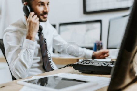 Photo for Selective focus of smiling bi-racial trader talking on telephone in office - Royalty Free Image