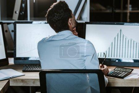 Photo pour Retour vue d'un commerçant biracial assis près d'un ordinateur avec des graphiques - image libre de droit
