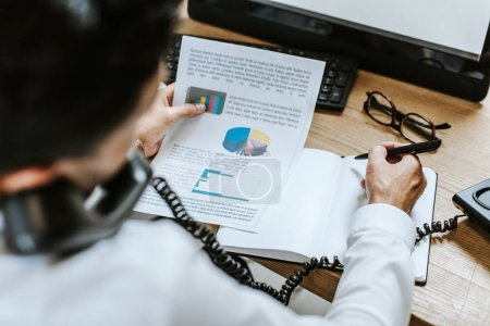 Photo for Selective focus of bi-racial trader talking on telephone and holding paper - Royalty Free Image