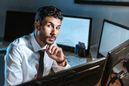 Photo pour Un trafiquant biracial pensif regardant une caméra dans son bureau - image libre de droit