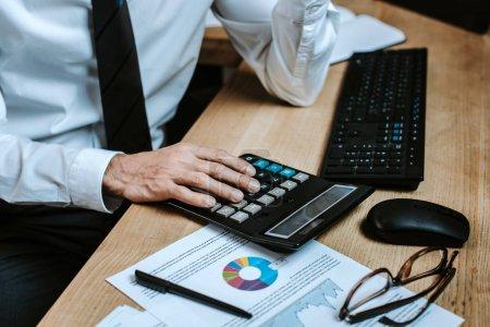 Photo pour Vue recadrée du commerçant bi-racial à l'aide d'une calculatrice et assis à table - image libre de droit