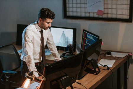 high angle view of bi-racial trader standing near computers in office