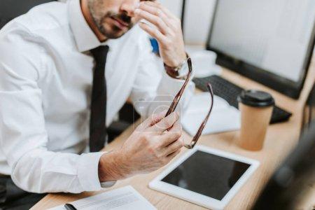 Photo pour Crochet vue d'un commerçant bi-racial fatigué tenant des lunettes au pouvoir - image libre de droit
