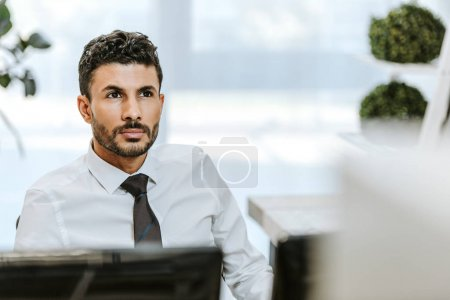 selective focus of handsome bi-racial trader looking away in office