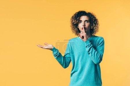 Photo pour Adolescent bouclé montrant shh geste et pointant avec la main de côté isolé sur jaune - image libre de droit