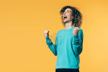 Photo for Excited curly teenager showing yes gesture and screaming isolated on yellow - Royalty Free Image